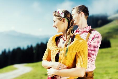Couple in Tracht on Alp mountain summit at vacation photo