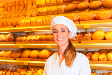 salesgirl: Female baker or saleswoman in her bakery selling fresh bread, pastries and bakery products