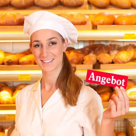 Female baker or saleswoman in her bakery selling fresh bread, pastries and bakery products, she hold a sign in her hand saying offer in German photo