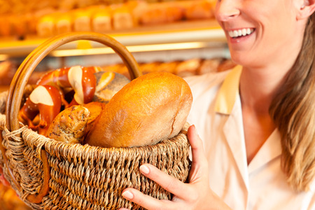 saleslady: Female baker or saleswoman in her bakery selling fresh bread, pastries and bakery products in basket
