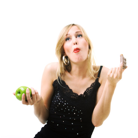 Woman eating candy instead of fresh apple photo