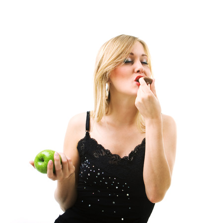 guilty pleasure: Food and healthy nutrition - Woman nibbling from chocolate and not from fruit Stock Photo