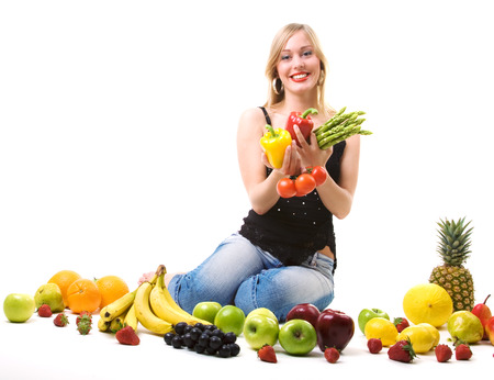 banana: Beautiful woman sitting amidst fruits holding vegetables Stock Photo