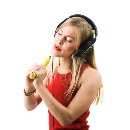 Beautiful blond girl using a banana as microphone photo