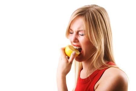 Woman having a nibble of a lemon making a grimace Standard-Bild