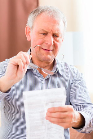 medicament: Old man reading  medicament package insert at home with glasses