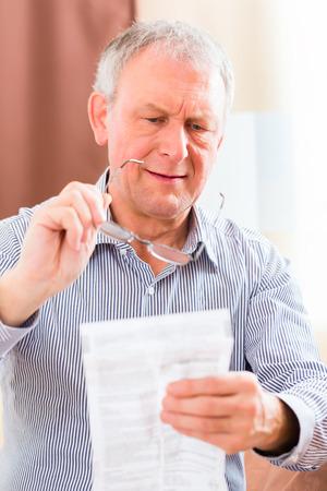 Oude man het lezen medicament bijsluiter thuis met een bril Stockfoto