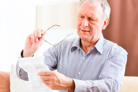 effects: Old man reading  medicament package insert at home with glasses