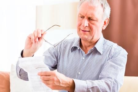 vidrio: Viejo hombre de lectura del paquete medicamento inserto en casa con gafas