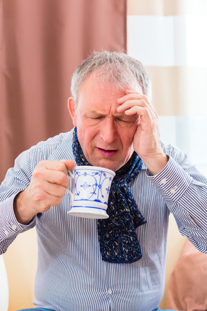 medicate: Old man drinking tea to cure bad cold or flu at home Stock Photo