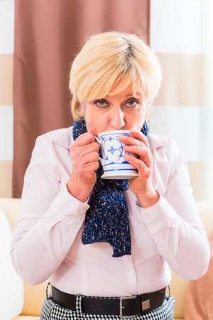 medicate: Old woman drinking tea to cure her bad cold or flu at home