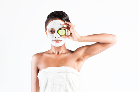 Young African woman in Studio doing body care with refreshing cucumber facial mask for young and beautiful skin and relaxation Stock Photo
