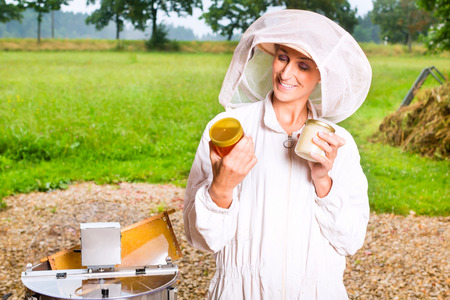 extractor: Female beekeeper filling honey with extractor in glass