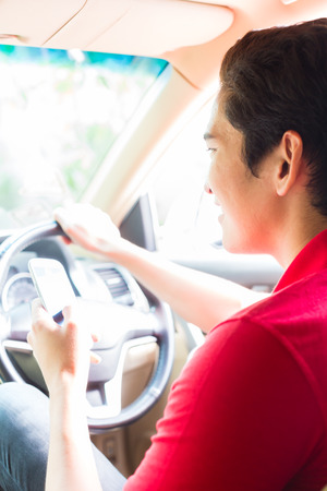 Asian young man texting message on mobile phone or smartphone while driving car photo