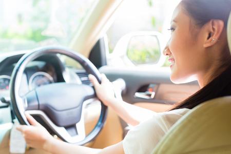 アジアの女性の運転新しい車