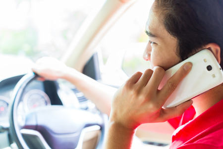 Asian young man telephoning with mobile phone or smartphone while driving car photo