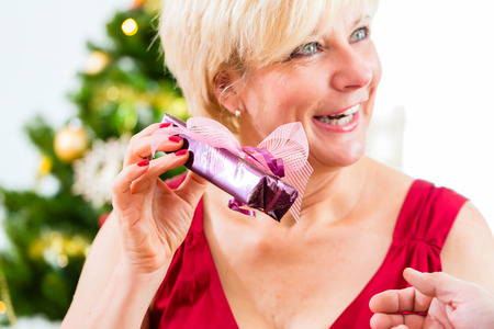 fulfil: Senior woman is curious about Christmas gift Stock Photo