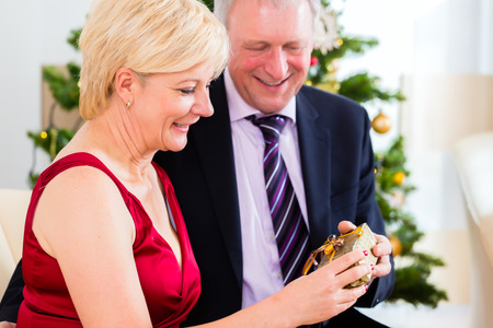 fulfil: Senior man and woman celebrating Christmas with presents and X-mas tree