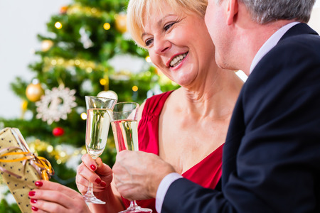 Senior man and woman celebrating Christmas eve with a glass of sparkling wine photo