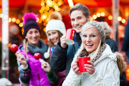 Přátelé pití svařené víno a jíst crystalized Appels na německém Vánoční trh