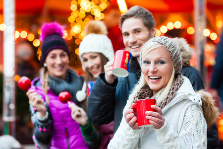 Friends drinking mulled wine and eating crystalized appels on German Christmas Market Stockfoto