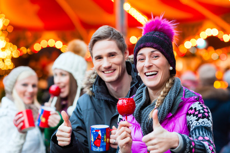 mulled: Friends drinking mulled wine and eating crystalized appels on German Christmas Market Stock Photo