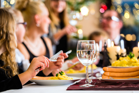 Family of Mother, father, children celebrating Christmas eve with traditional dinner Wiener sausages and potato salad photo