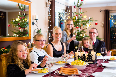 traditional christmas dinner: Family of Mother, father, children celebrating Christmas eve with traditional dinner Wiener sausages and potato salad