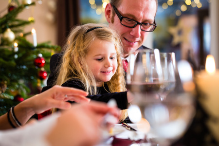 traditional christmas dinner: parents and children toasting with wine and water at Christmas eve dinner