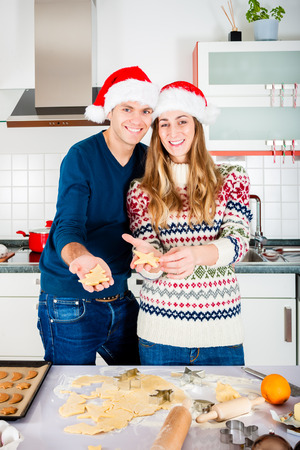Man and woman baking Christmas cookies at home in domestic kitchen photo
