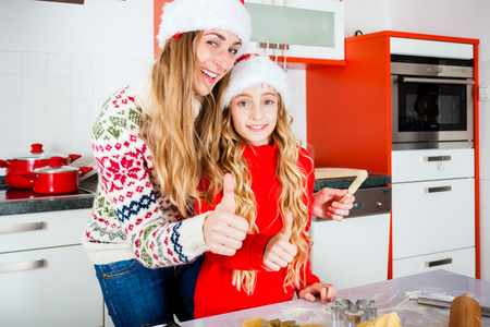 Mother and daughter baking X-mas cookies at home in domestic kitchen photo