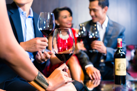 Asian friends chatting and drinking red wine Stock Photo
