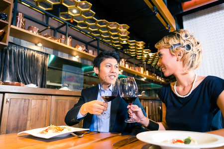 Asian couple toasting with red wine photo