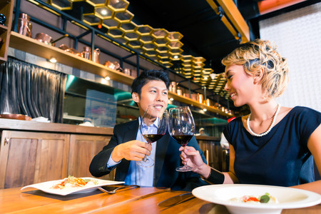 lifestyle dining: Asian couple toasting with red wine