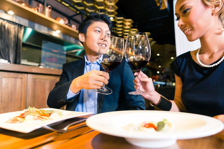 Asian couple toasting in restaurant Stock Photo