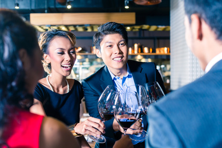 Asian friends toasting with red wine in bar or restaurant