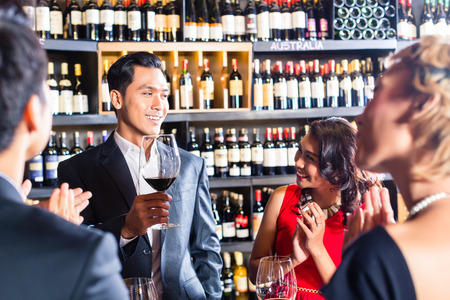 Asian friends celebrating with wine Stock Photo
