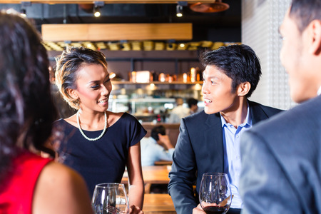 dining out: Asian friends sitting in restaurant Stock Photo