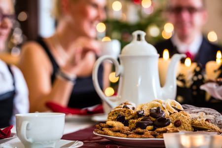 Family celebrating Christmas with drinking coffee and X-mas cookies photo