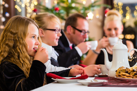 Parents and children celebrating Christmas with drinking coffee eating and X-mas cookies photo