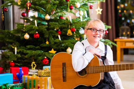 christmas day: Girl playing guitar on Christmas day Stock Photo