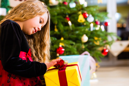 christmas day: Girl opening present on Christmas day under tree Stock Photo