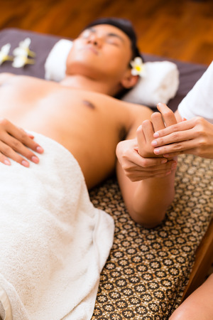 sensual massage: Indonesian Asian man in wellness beauty spa having aroma therapy hand massage with essential oil, looking relaxed