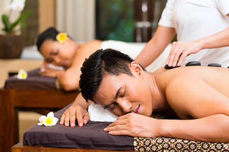 spas: Indonesian Asian couple man and woman in wellness beauty spa having aroma therapy massage with essential oil, looking relaxed