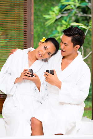 sensual massage: Indonesian Asian couple man and woman in wellness beauty spa having aroma therapy massage with essential oil, looking relaxed