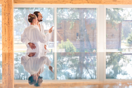 bath gown: Couple on pool looking relaxed throw window of wellness spa wearing bath robe Stock Photo