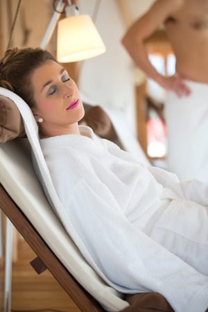 bath gown: Woman in bath robe relaxing or sleeping on swing lounger in wellness spa relaxation room Stock Photo