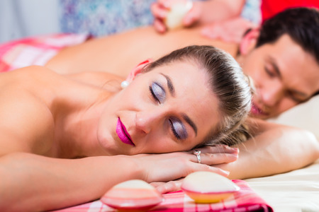 Couple having relaxing sea shell back massage in wellness spa photo