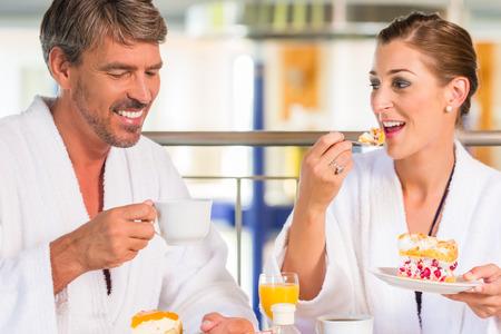 pareja comiendo: La mujer y el hombre comiendo merienda con café y tarta en balneario