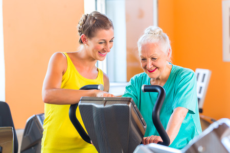 Senior woman with trainer in fitness club exercising on stationary bike for a workout photo